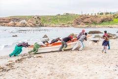 I pescatori muove la loro barca verso sopra il segno di alta marea Immagini Stock Libere da Diritti