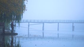 I pescatori profilano e cantano mattina sul vecchio ponte di legno del lago archivi video