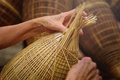 I pescatori vietnamiti stanno facendo il panieraio per l'attrezzatura di pesca immagine stock