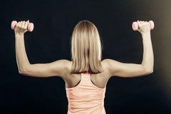 I pesi di sollevamento della ragazza sportiva di forma fisica indietro osservano immagini stock