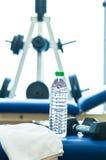 I pesi si levano in piedi, banco di una ginnastica, bottiglia di acqua del tovagliolo Fotografia Stock