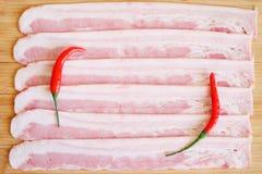I pezzi appetitosi di bacon della carne di maiale e di peperoncini rossi si trovano su una superficie di legno naturale Luce del  fotografia stock libera da diritti