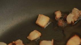 I pezzi del bacon su una padella calda sono tostati stock footage