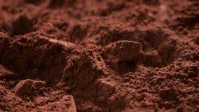 I pezzi del cioccolato cadono in cacao in polvere - scorrevole della macchina fotografica archivi video