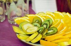 I pezzi di arancia, di kiwi e di banana si trovano su un piatto immagini stock libere da diritti