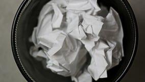 I pezzi di carta sgualciti sono caduto nella pattumiera stock footage