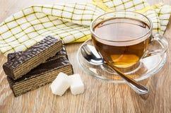 I pezzi di cialda del cioccolato agglutinano, tazza di tè, lo zucchero fotografia stock libera da diritti