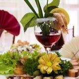 I pezzi di pesce su un vassoio con un bicchiere di vino e un gamberetto Fotografie Stock