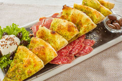 I pezzi di pizza risiedono nelle verdure crude del eith sulla tavola Pezzo della pizza Fotografia Stock Libera da Diritti