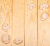 I pezzi di primo piano crudo del cavolfiore su fondo accendono il legno Fotografia Stock