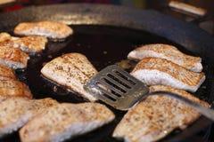 I pezzi di salmoni friggono in una grande padella Fotografia Stock