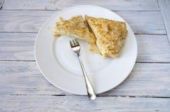 I pezzi di soffio agglutinano su un piatto bianco con una forcella del dessert Fotografia Stock Libera da Diritti