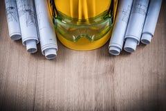 I piani della costruzione dei vetri di protezione ed il casco della costruzione sopra corteggiano Fotografia Stock