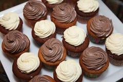 I piatti di porcellana della foto con 16 muffin con cioccolata bianca si sviluppa a spirale crema Immagini Stock Libere da Diritti