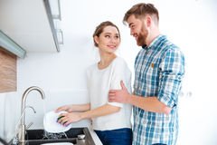 I piatti e l'uomo di lavaggio della donna vuole aiutarlo Fotografia Stock