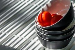 I piatti hanno impilato sui pomodori della tabella tre Fotografia Stock Libera da Diritti