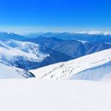 I picchi di montagne nevosi dell'inverno abbelliscono contro le sedere soleggiate blu del cielo Fotografie Stock Libere da Diritti