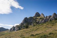 I picchi rocciosi drammatici hanno messo contro una catena montuosa e un cielo blu Immagine Stock