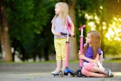 I piccoli bambini che imparano guidare i motorini in una città parcheggiano sulla sera soleggiata dell'estate Bambine sveglie che Immagine Stock