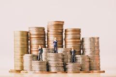 I piccoli businessmans calcola la condizione sulla pila delle monete fotografia stock libera da diritti