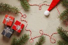 I piccoli contenitori di regalo di Natale su fondo grigio con abete si ramifica Composizione nel buon anno ed in natale Vista sup Immagini Stock