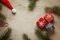 I piccoli contenitori di regalo di Natale su fondo grigio con abete si ramifica Composizione nel buon anno ed in natale Vista sup Immagine Stock Libera da Diritti