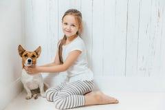I piccoli giochi da bambini femminili adorabili con il suo cane nella stanza bianca, si siedono fotografie stock