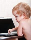 I piccoli giochi da bambini su un computer portatile Immagine Stock Libera da Diritti