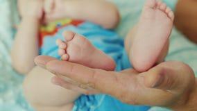 I piccoli piedi di piedi del bambino su una grande palma generano stock footage