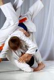 I piccoli sportivi sta facendo i tiri di judo Fotografia Stock