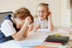 I piccoli studenti allegri dividono lo stesso scrittorio Immagini Stock Libere da Diritti