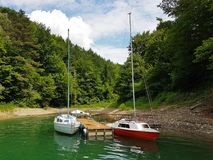 I piccoli yacht della navigazione di navigazione costiera sono attraccati al pilastro in un porto pittoresco Stile di vita presti fotografia stock libera da diritti