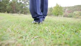 I piedi degli uomini in scarpe vanno sull'erba stock footage
