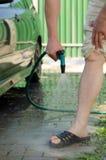 I piedi degli uomini sono innaffiati con acqua da un tubo flessibile Fotografia Stock
