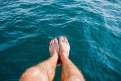 I piedi degli uomini sui precedenti del mare blu Immagini Stock Libere da Diritti