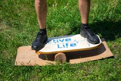 I piedi degli uomini sulla piattaforma per equilibrio imbarcano su un fondo dei gras verdi Fotografia Stock