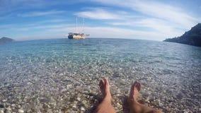 I piedi degli uomini sulla spiaggia sul mare e sulla nave blu della riva archivi video