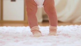 I piedi del bambino che fanno un passo sulla coperta tricottata della peluche archivi video