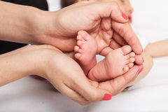 I piedi del bambino in madre passa i piedi del bambino in mani della madre immagine stock libera da diritti