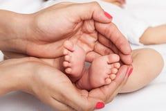 I piedi del bambino in madre passa i piedi del bambino in mani della madre fotografie stock libere da diritti