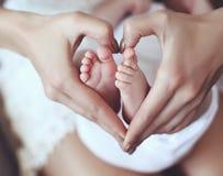 I piedi del bambino in mamma passa la tenuta loro nella forma del cuore Fotografie Stock Libere da Diritti