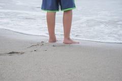 I piedi del bambino in sabbia sulla riva Immagine Stock