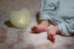 I piedi del neonato a letto si chiudono su Concetto 'nucleo familiare' felice Bella immagine concettuale di maternità Utile come  Fotografie Stock