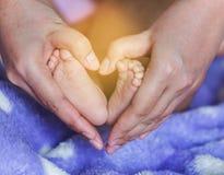 I piedi del neonato nella madre passa il cuore a forma di Fotografie Stock