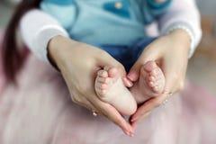 I piedi del ` s del bambino nella mano e nel cuore del ` s della madre modellano immagini stock libere da diritti