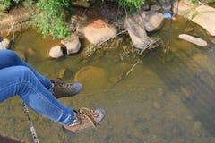 I piedi del viaggiatore che si rilassano sul fiume sorgono Fotografie Stock Libere da Diritti