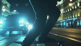 I piedi dell'uomo del skateboarder guida attraverso l'attraversamento della strada di città di notte stock footage