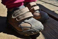 I piedi della bambina in Velcro beige inizializza la condizione sul pavimento di legno Fotografia Stock