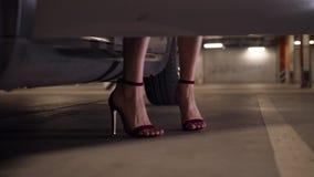 I piedi della donna in alte scarpe tallonate che ottengono in automobile video d archivio
