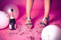 I piedi della donna con i coriandoli sul pavimento e sul champagne Fotografia Stock